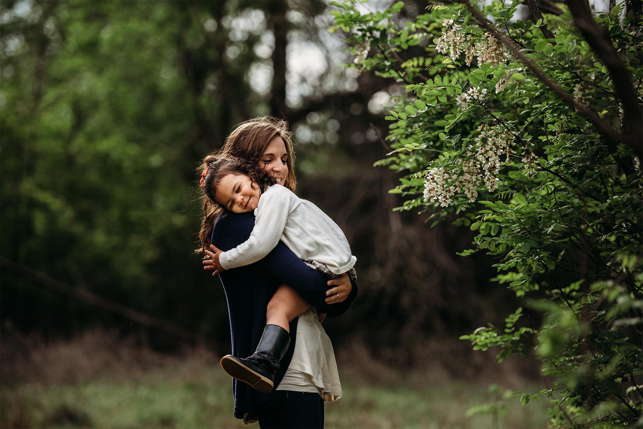 mom cuddling daughter