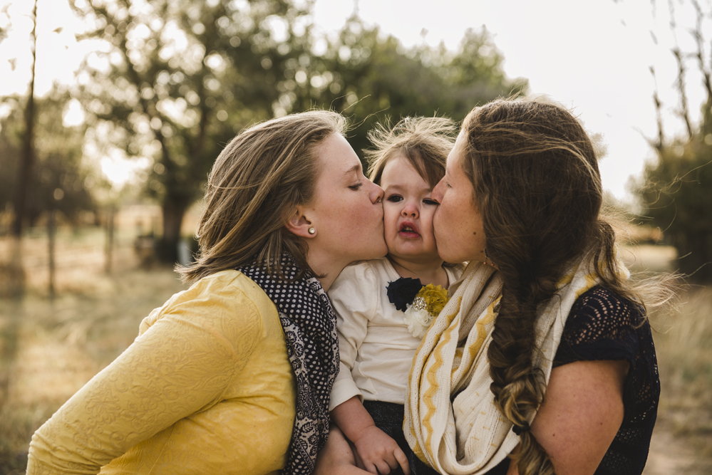 sisters-kissing-toddler