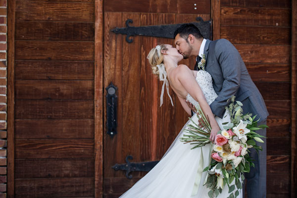 groom-tipping-bride-kiss