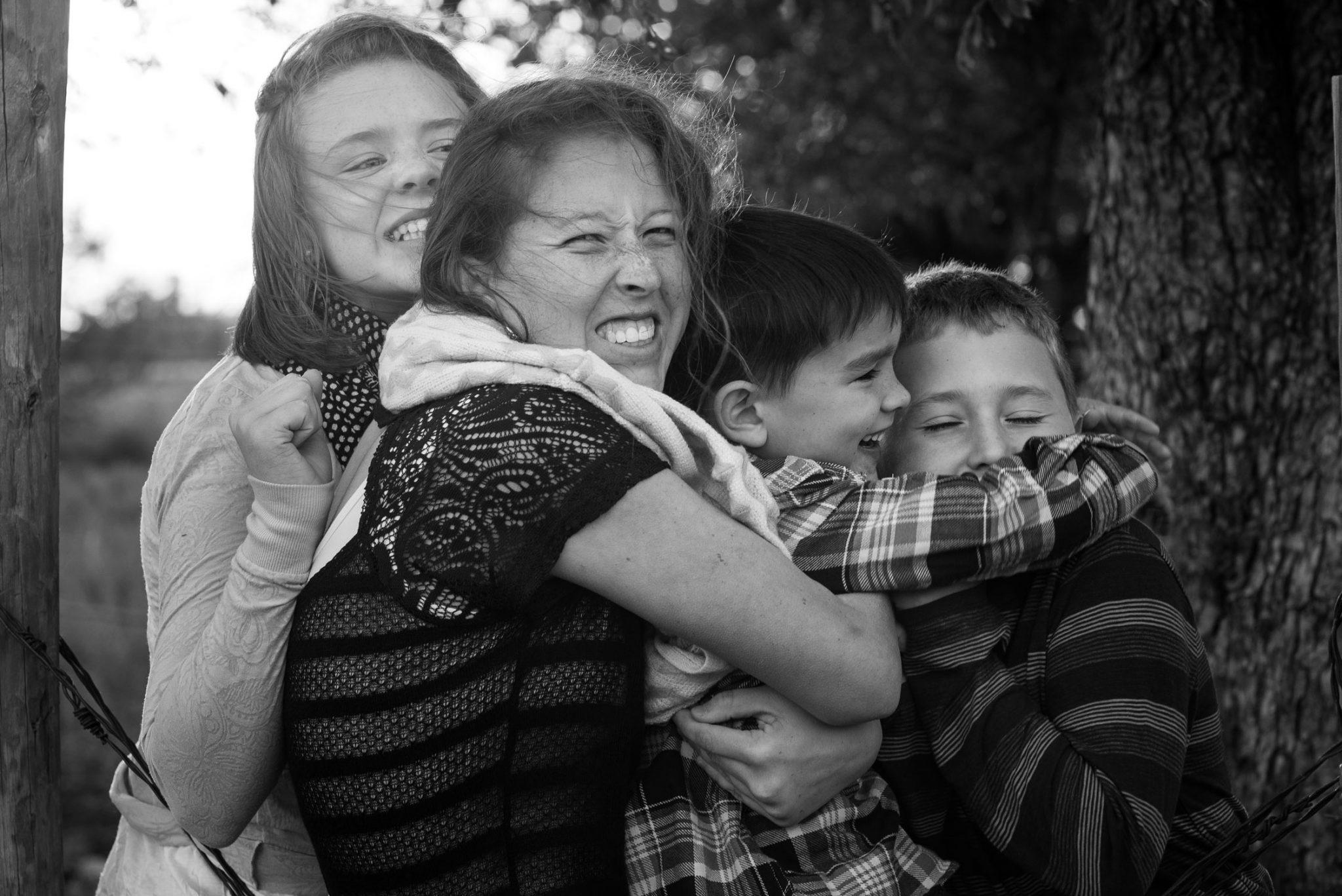 siblings hugging on fence