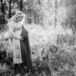 pregnant woman standing in forest