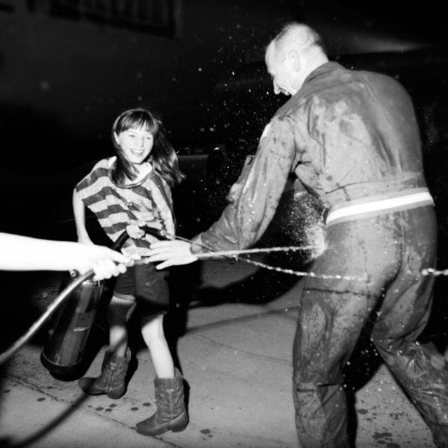 girls dousing dad in water