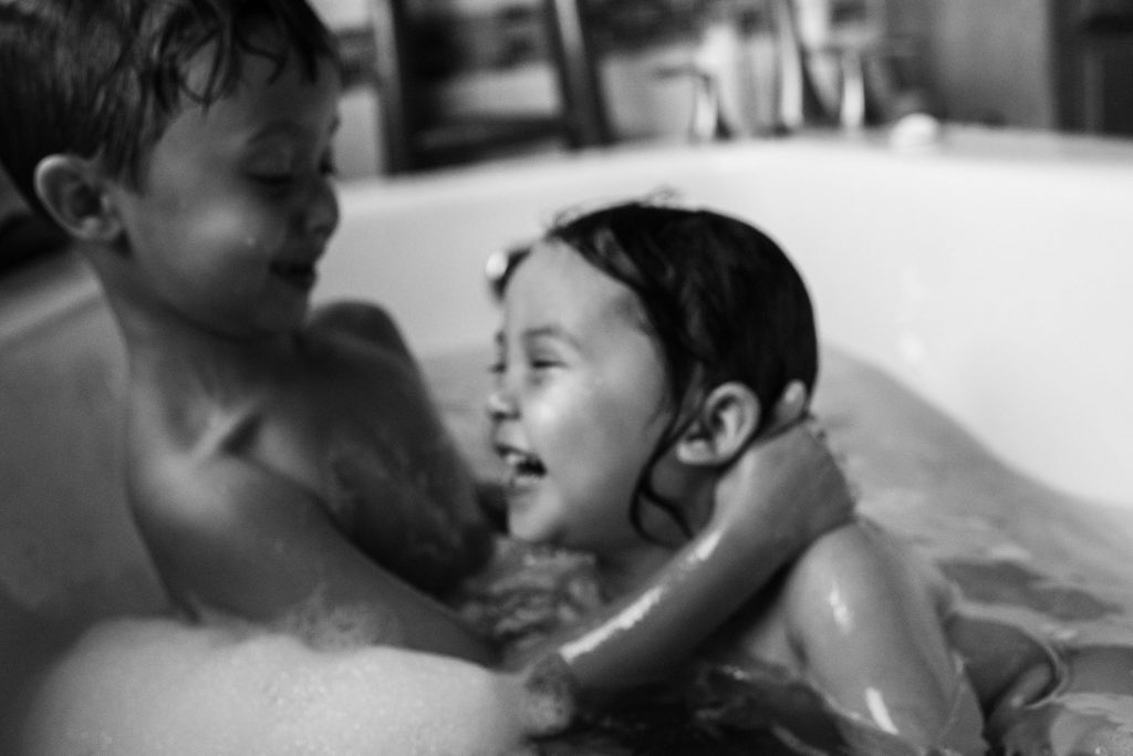 boy and girl playing and hugging in bath