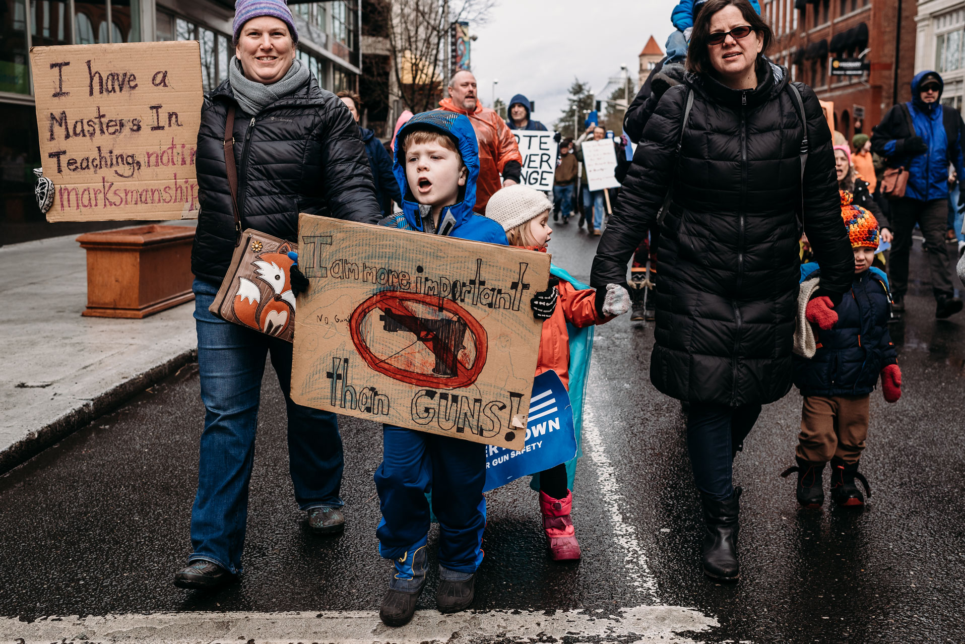 kid holding sign with family