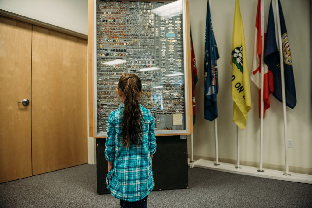 girl standing in front of case of medals