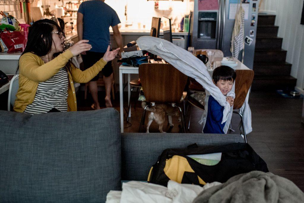 mom tossing boys cape