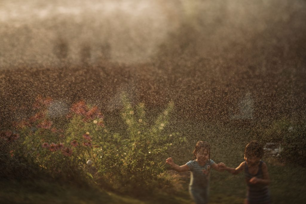 boy and girl running under water