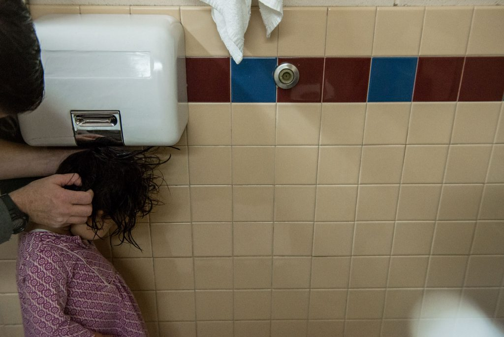 girl blow drying hair under hand dryer
