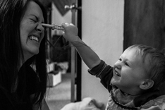boy sticking pen in mom's eye