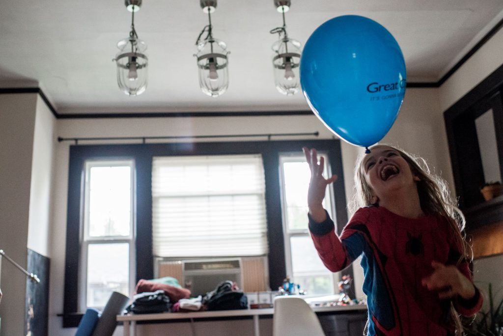 girl bopping balloon with head