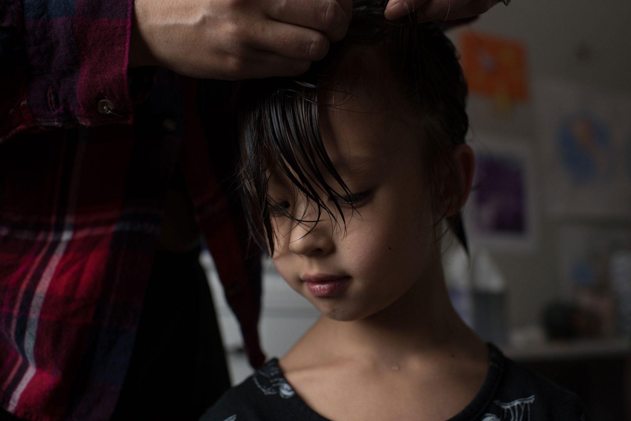 mom braiding child's hair