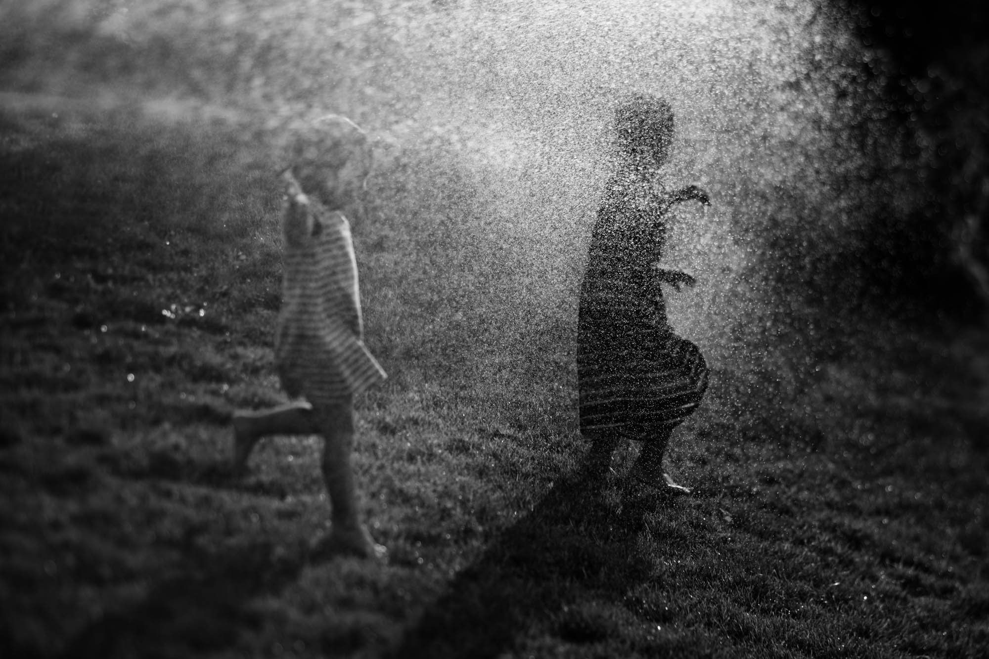 girls playing in sprinklers