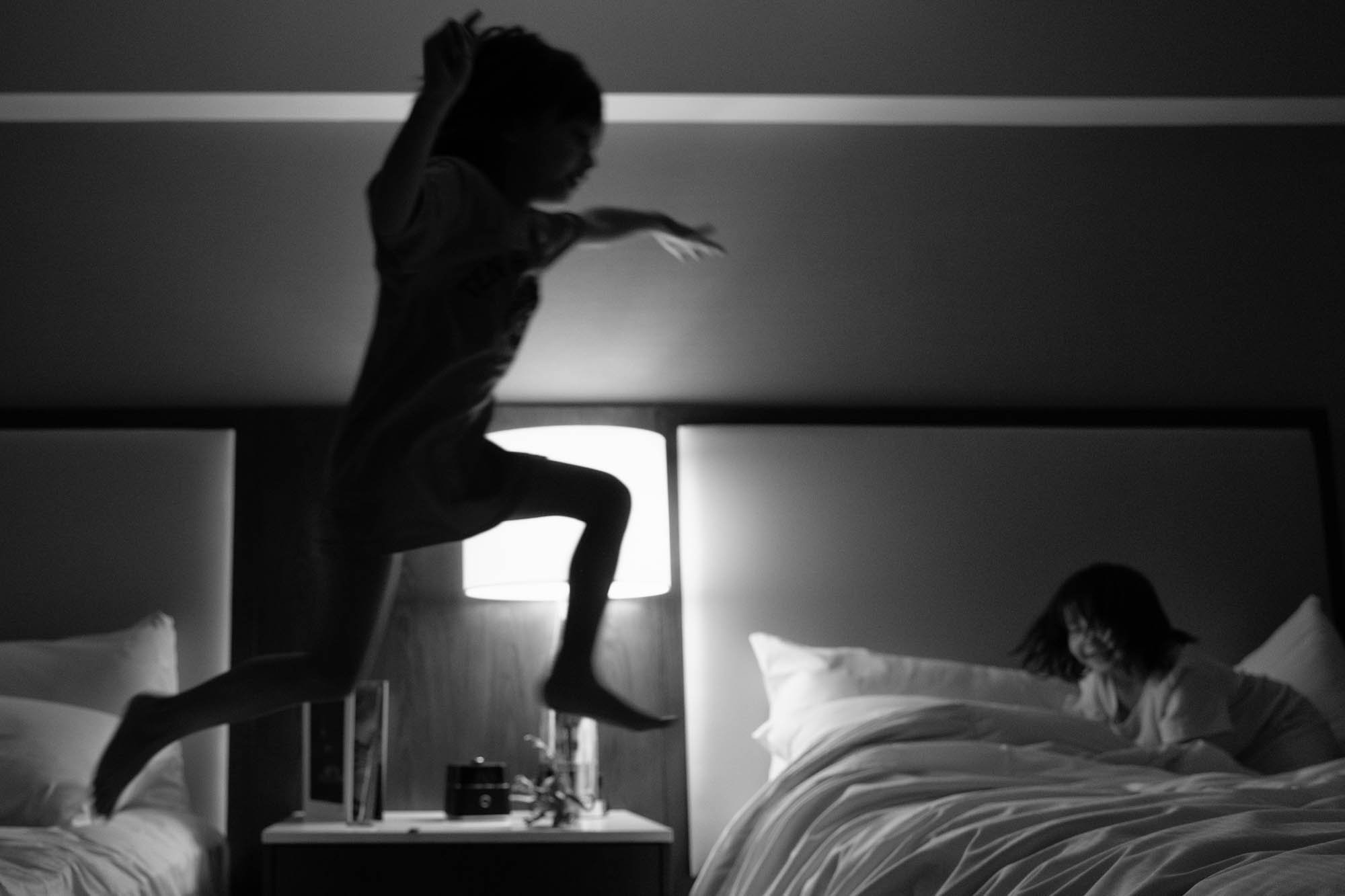 girl jumping over beds