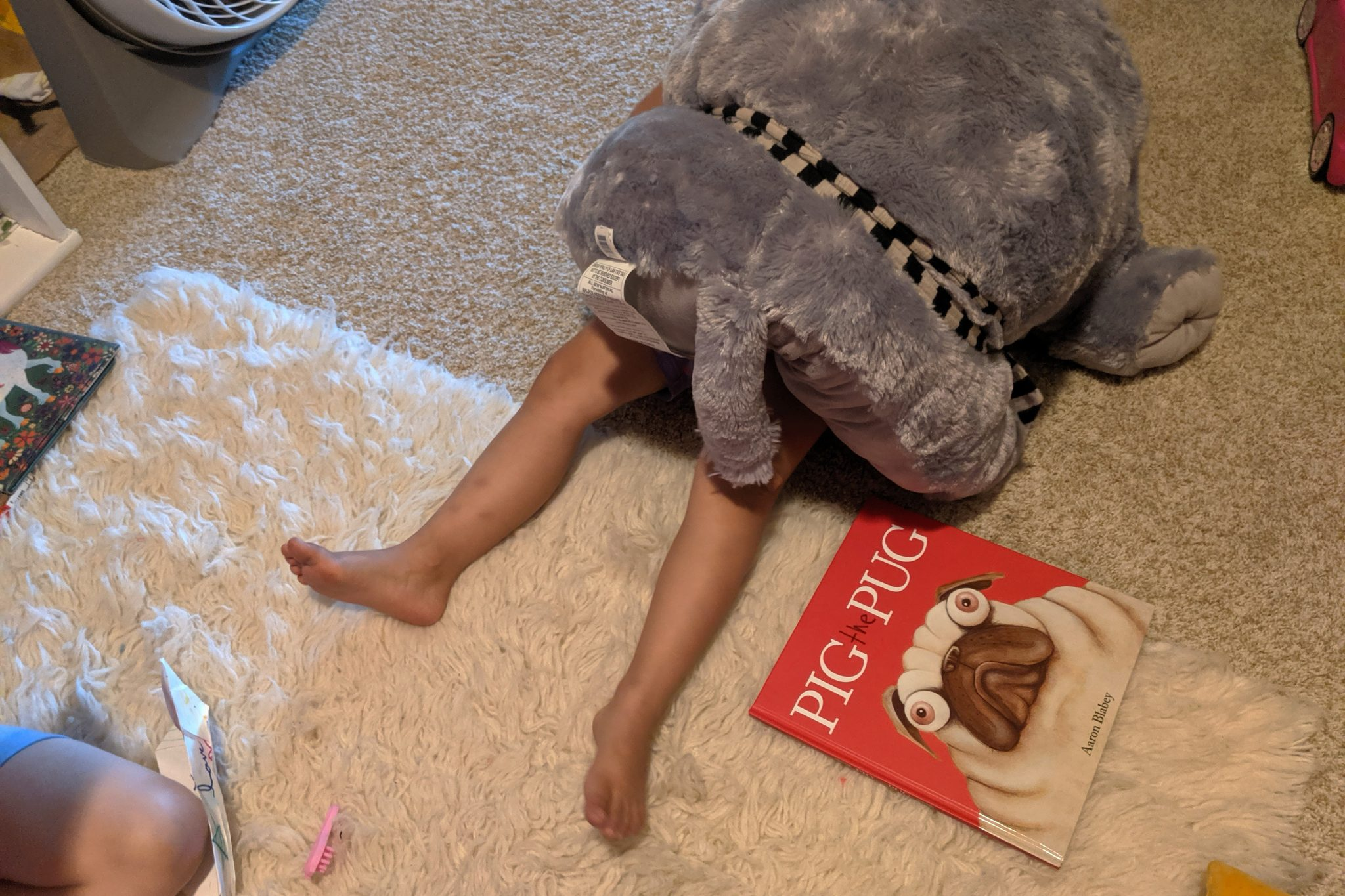 child on floor covered by stuffy