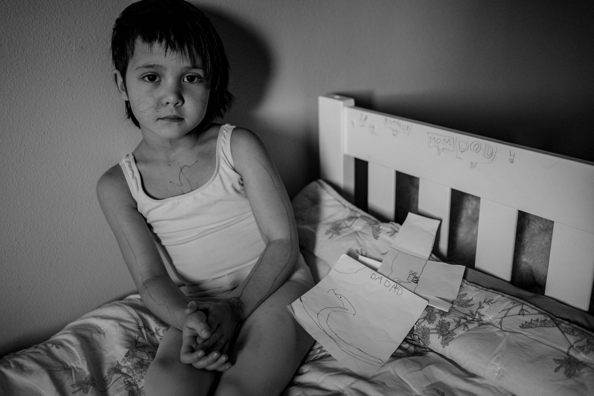 portrait of girl on her bed with writing on her face