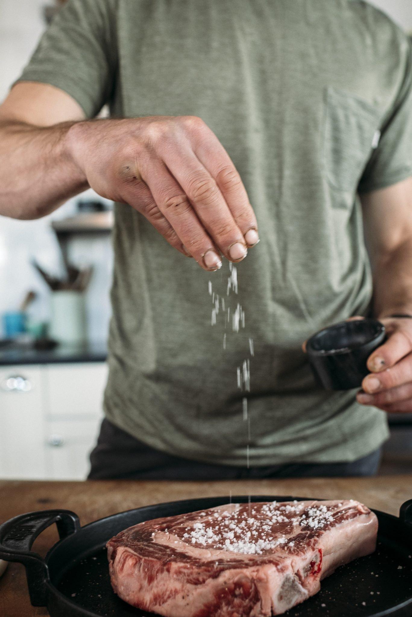 man seasoning steak