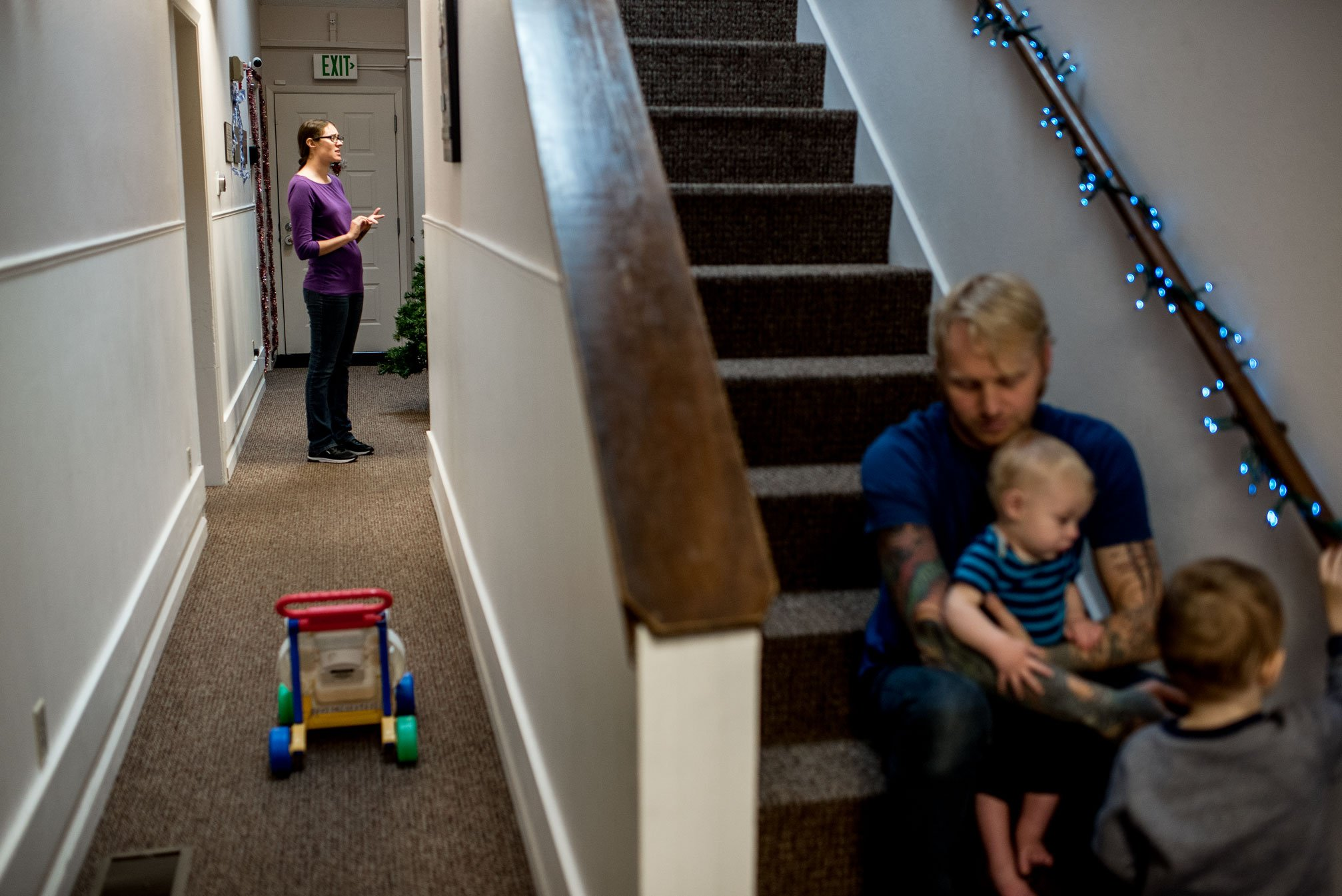 dad on stairs playing with kids mom on phone