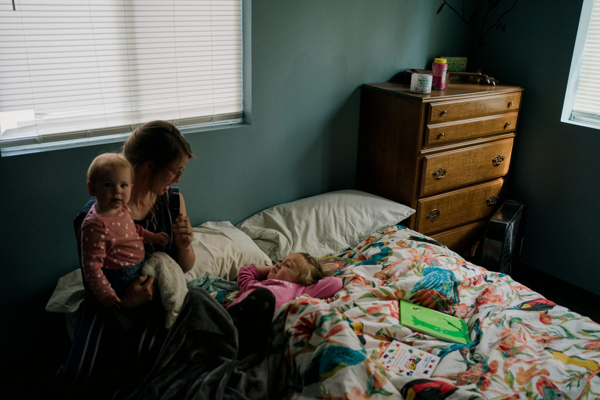 mom waking up toddler in bed