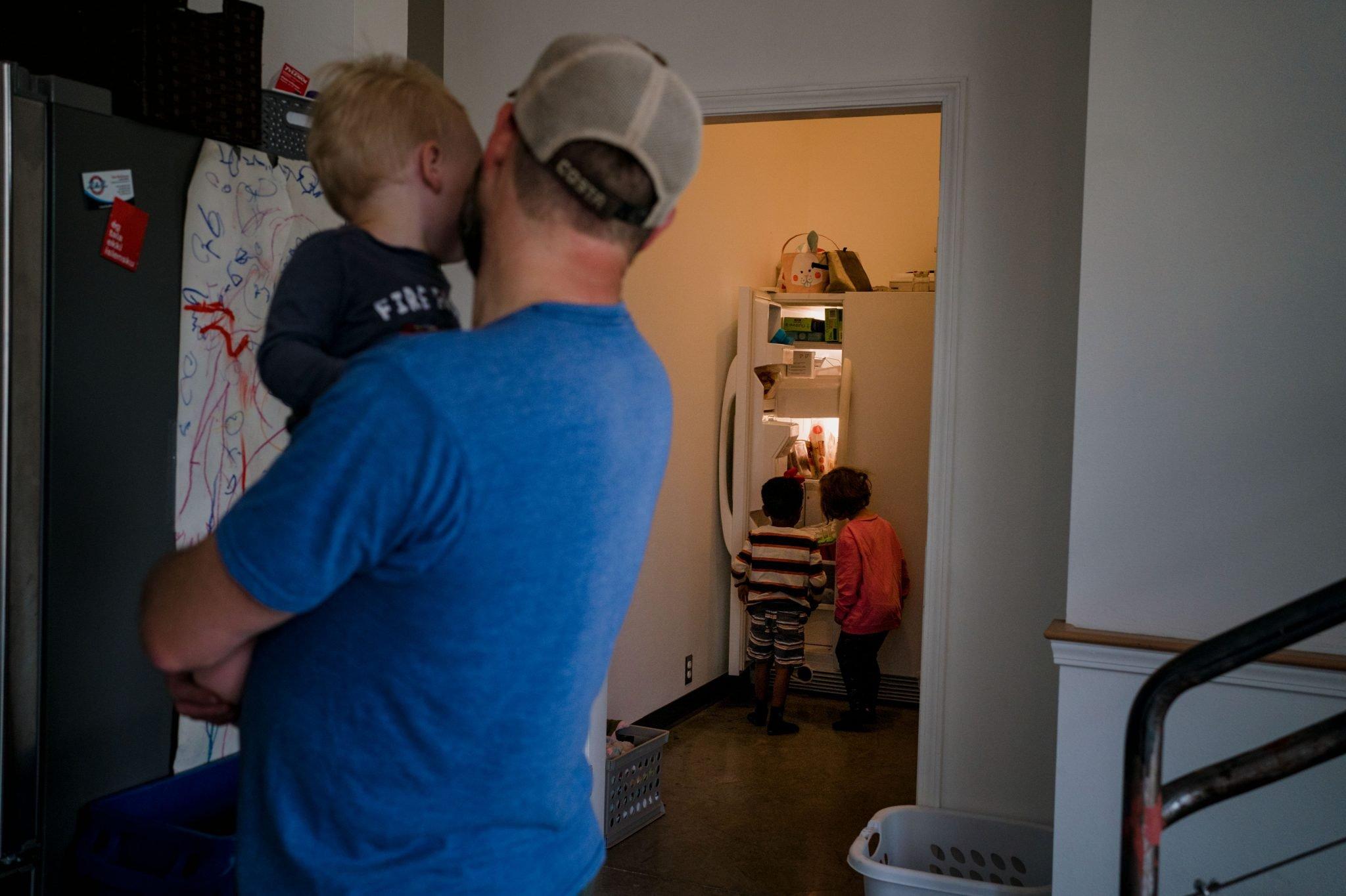 dad watching toddlers climb into fridge