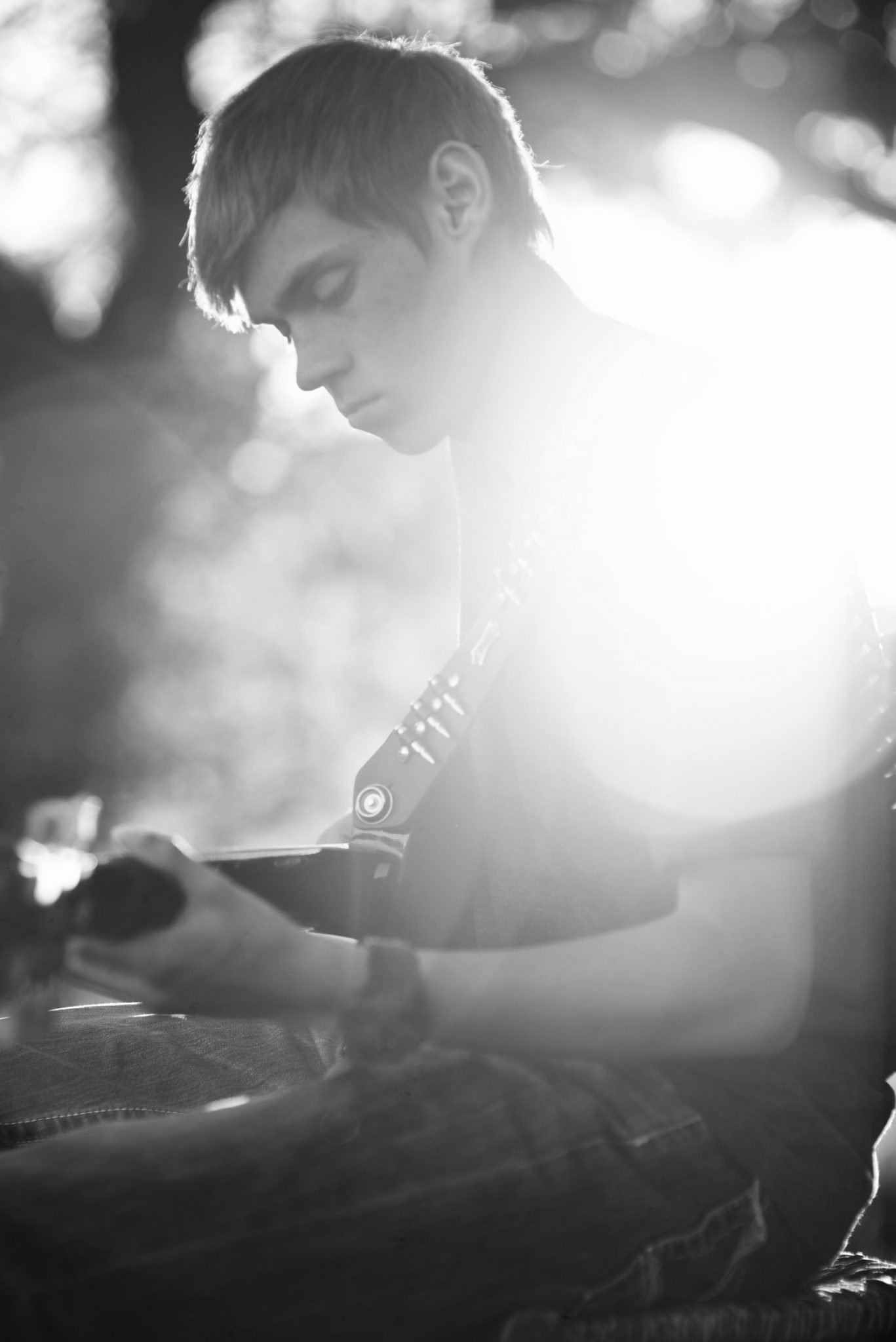 boy playing guitar with light streaming behind him