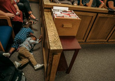 kids crawling around benches in courtroom during proceeding