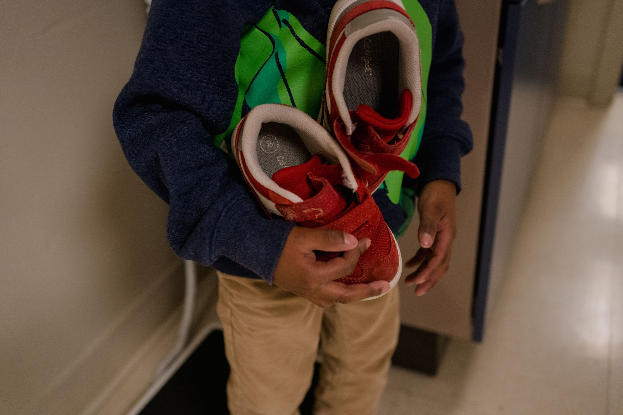 boy holding shoes while being measured